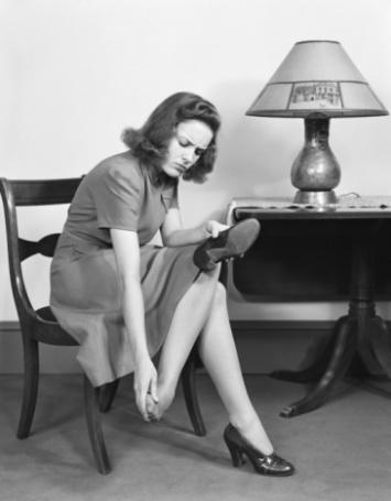 1950s women rubbing feet; heals; pain